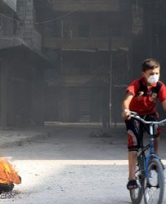 ALEPPO, SYRIA - AUGUST 4: Syrian children ride bikes as Syrian opponents burn tires to block the ground visibility of the war crafts belonging to the Russian Army and Assad regime forces at an opposition controlled neighborhood in Aleppo, Syria on August 4, 2016.  Ibrahim Ebu Leys / Anadolu Agency